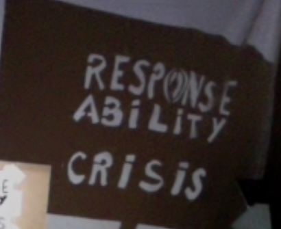 Wryly, The words Responsibility Crisis read down the image in light on a dark horizontal rectangle, warping at the top right on the ripple of a white sheet. The edge of a cardboard frame, with words cut in paper pokes in from the bottom left.