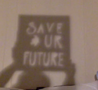"""Save Ur Future, """"Save UR Future"""" in light letters and an Earth cut out on a shadow rectangle, held up by two shadow hands, with shadow arms and head, on a white wall."""