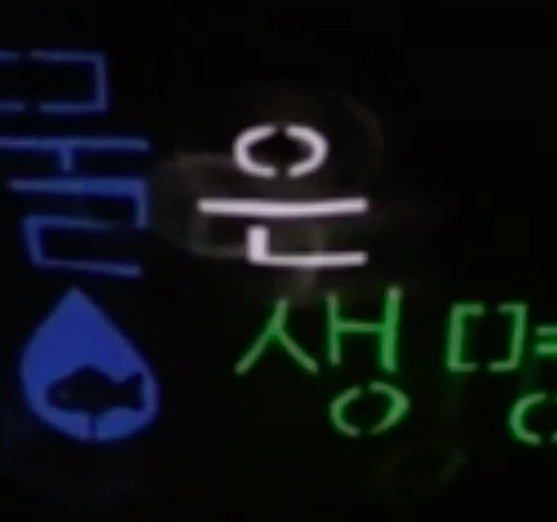 """Mul Eun Seng Myong, Mul Eun Seng Myong. """"Water is life"""" appears on a black background. """"Mul"""" (water) is in vibrant blue. """"Eun"""" is in white. """"Seng Myong"""" (Life) is in vibrant green. Below """"Mul"""" is a blue water drop and a fish silhouette swims in the water drop."""