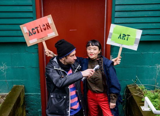 """In this photo by Marjo Wright, taken for the 2021 rEvolver Theatre Festival, the artists are standing side by side on stairs and smiling. The ground is wet and Wryly, on the left side on the first step, is holding a transparent plastic umbrella high up. The umbrella has an attached word """"Action"""" made of red velvety fabric pieces. Minah occupying the second step on the right, is wearing bright red lipstick that matches her pants. Dangling triangular earrings with pink knitting swing above her indigo rain jacket. Wryly is wearing a black toque that matches the pants, a pink and blue stripe sweater under a dark rubber rain coat."""