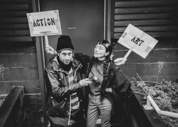 """In this black and white photo by Marjo Wright, taken for the 2021 rEvolver Theatre Festival, artists are holding wooden sticks of two paper cut signs framed by cardboard. Minah is stretching her right arm to hold """"Action"""" sign behind and above Wryly's right shoulder and head. She is intensely looking at the sign. Wryly is stretching their left arm across Minah's back to hold """"Art"""" sign above Minah's left shoulder. Wryly is pointing the sign with a flashlight and boldly gazing right at you. They are standing in front of a door with brick and wooden wall around it."""