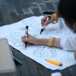 Participants work from their tents, first examining their clothing and discussing the origins of those clothes, then plotting them onto the Potentcity.space website to see a visual representation of the pattern s of clothing migration. In the second workshop, participants discuss climate change, then create shadow signs expressing their thoughts and feelings to project onto their tent or other available surface to capture and upload onto Potentcity.space to create a mosaic of the Earth from the collected shadow signs. The light wanes and dusk comes as the second workshop progresses. A tent with the QR code to download the Home squat Home mobile app in Korean can be seen on the stage.